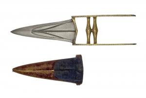 Dolch (Katar) NW-Indien, 18. Jh. Trianguläre, tief profilierte Klinge. Die massive Klinge ist aus Gefügedamast geschmiedet. Das Gefäß besteht aus zwei Längsbügeln mit zwei quergesetzten in der Mitte verdickten fazettierten Spindeln als Handhabe. Alle sichtbaren Gefäßteile sind flächig vergoldet und graviert. Ges.L.: 35,3 cm, Klingenl.: 18,4 cm, Inv.-Nr. SUW.615